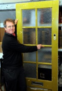 Auctioneer Chris Albury with the front door from Paul McCartney's family home in Forthlin Road, Allerton, Liverpool
