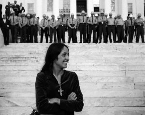 Joan Baez, folk singer, in front of State Troopers, Montgomery Alabama State House. Conclusion of Selma To Montgomery Alabama Civil Rights March - March 25, 1965