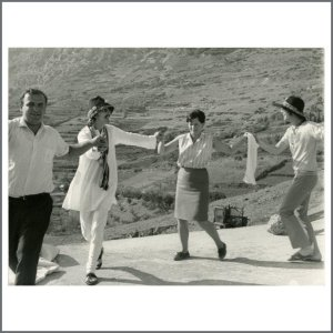 An original vintage 1960s black and white photograph of John Lennon and George Harrison. The image shows the pair dancing with locals in the Greek hills in late July 1967. The Beatles and their entourage travelled to Greece in July 1967 to view some Greek islands with the intent to purchase land and/or property. The photo is printed on vintage Agfa photographic paper. It measures 24cm x 18.25cm (9.5 inches x 7.2 inches).