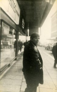 """""""George Harrison walking by Timothy Whites department store in Liverpool in early 1963,"""""""