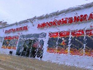 Взгляд на витрину магазина из машины во время ливня (в Великих Луках)