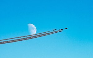 The Red Arrows fly past moon above RAF Scampton, Lincolnshire by Claire Hartley