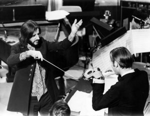 Beatles drummer Ringo Starr acting as conductor during a break in the filming of a Yorkshire Television Christmas programme at Leeds studios. With him is George Martin. January 1970.