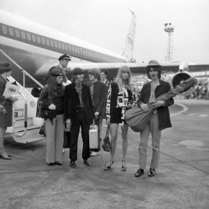 George Harrison and his wife Pattie (right), and Ringo Starr with his wife Maureen, arrive at London's Heathrow Airport after travelling from San Francisco. Behind them (centre) is Peter Asher, brother of Paul McCartney's girlfriend Jane Asher.