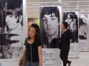 Passers-by walk past images of the British rock group Beatles members displayed at a subway concourse in Tokyo, Thursday, June 29, 2006. The legendary musicians landed in Japan for the first time on this day 40 years ago. Some shops and their fan clubs have arranged special events to celebrate the 40th anniversary for their Japanese tour of performance.