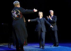 Elton John (L) greets Democratic presidential candidate and U.S. senator Hillary Clinton (D-NY) and former President Bill Clinton (R) as he takes the stage at a fundraising concert for Clinton's campaign at New York's Radio City Music Hall April 9, 2008.