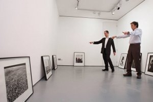 Sir Paul McCartney (L) looks at photos dated from the 1960s up until the late 1990s, including images shot by his late wife Linda, as he hangs them at an exhibition entitled Linda McCartney Photographs at the James Hyman Gallery, April 22, 2008 in London, England.