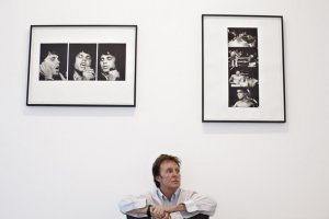 Sir Paul McCartney sits beneath photos dated from the 1960s up until the late 1990s, including images shot by his late wife Linda, as he hangs them at an exhibition entitled Linda McCartney Photographs at the James Hyman Gallery, April 21, 2008 in London, England.