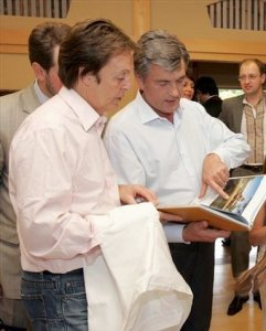Former Beatle Sir Paul McCartney tries a traditional Ukrainian hand-made shirt offered by Ukrainian President Viktor Yushchenko during their meeting in Kiev, Ukraine, Sunday, June 15, 2008