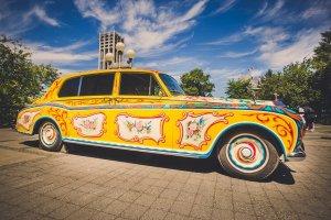 Психоделический Rolls-Royce Джона Леннона возвращается в Великобританию в честь юбилея Sgt. Pepper's Lonely Hearts Club Band, сообщает  Billboard .  Музыкант заказал себе этот автомобиль в декабре 1964 года. Водительских прав у Джона не было, но в случае с Rolls-Royce Phantom V это не имело значения, поскольку он рассчитан на езду с шофером.  Пассажирский салон в машине огромный. Леннон попросил установить там проигрыватели, радиотелефон и холодильник.  В 1966-м машина получила небольшие повреждения во время съемок Джона в фильме How I Won the War. Музыкант отдал Rolls-Royce в ремонт и заказал дополнительные нововведения (в машине появился телевизор, а также сиденье, трансформируемое в кровать).  На следующий год, во время записи Sgt. Pepper's Lonely Hearts Club Band, Леннон отправил автомобиль в компанию JP Fallon для дальнейшей переделки. Результат соответствовал психоделическому характеру альбома.  В 1970 году Джон забрал машину в США. Он ездил на ней сам и одалживал ее другим знаменитостям, в том числе Бобу Дилану и группе The Rolling Stones.  Из-за ситуации с налогами музыкант передал автомобиль в Cooper Hewitt Museum of Design. В 1985 году машину продали на аукционе канадскому предпринимателю Джимми Паттисону за $2,3 млн. Впоследствии Паттисон подарил Rolls-Royce провинции Британская Колумбия.  В этом месяце машина возвращается в Британию. Она станет экспонатом выставки The Great Eight Phantoms, которую проводят компания Rolls-Royce и аукционный дом Bonham's. Как передает  Forbes , увидеть экспозицию можно будет в Лондоне.